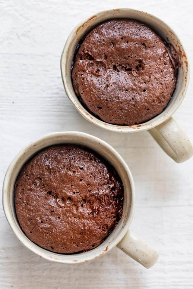Two mugs with the chocolate mug cake after microwaving