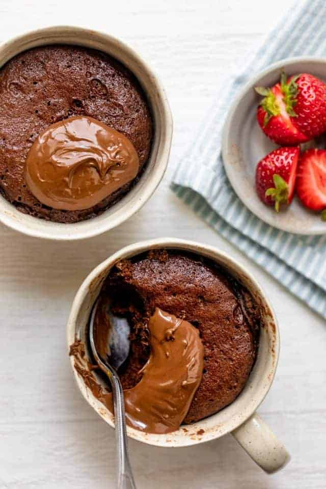 Nutella mug cake divided into two mugs made in one mug in one minute for one person, this Crumbly Nutella Mugcake is the perfect quick treat for a sweet tooth!
