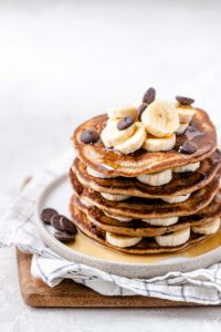 Stack of oat flour pancakes with bananas between the slices