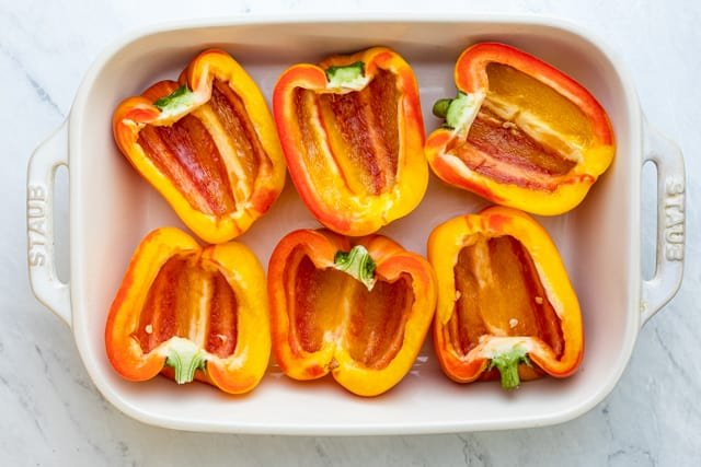 6 hallowed peppers halves on a white baking dish