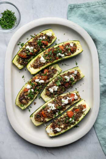 Top down shot of Quinoa Stuffed Zucchini boats on a large white plate