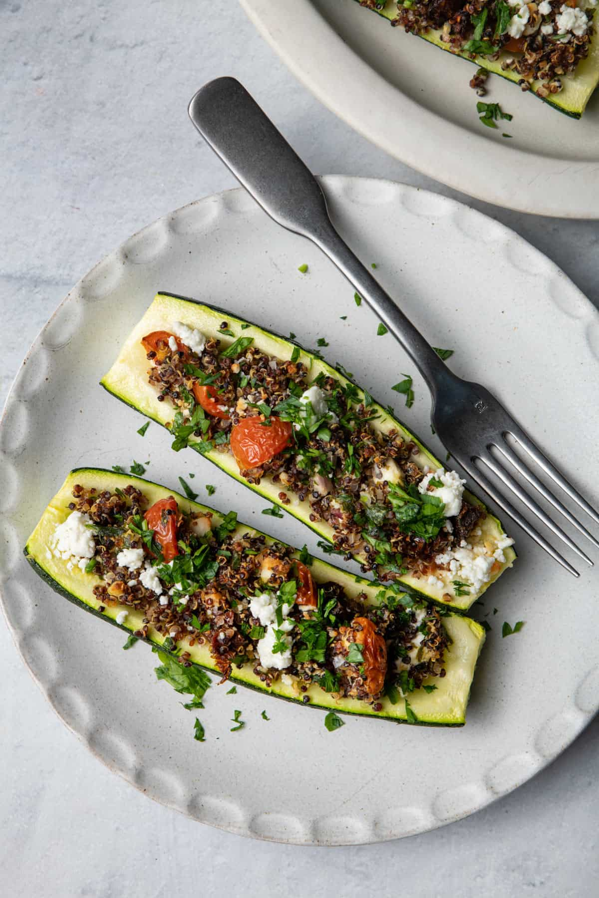 Plate with two quinoa stuffed zucchini boats and fork