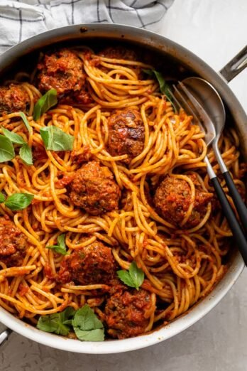 Large skillet of spaghetti and meatballs topped with basil