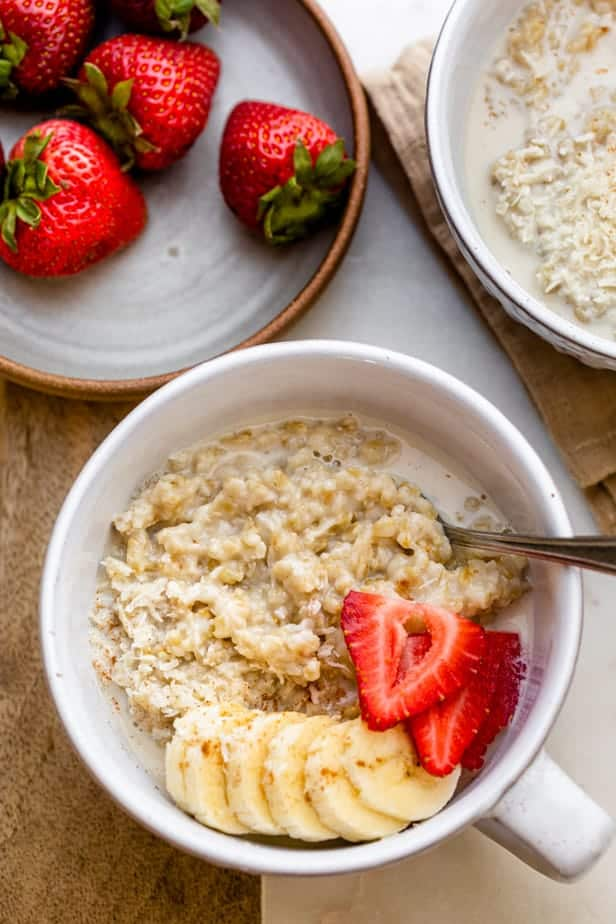 Close up shot of steel cut oatmeal topped with banana, strawberries and coconut