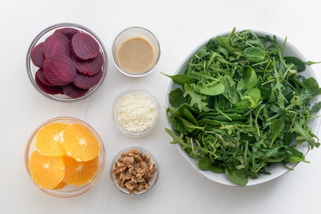 Ingredients to make the salad: arugula and spinach mix, beets, oranges, nuts, feta cheese and the homemade dressing