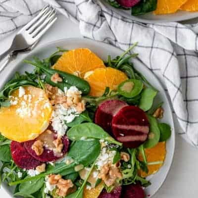 Beet orange salad topped with feta cheese and walnuts