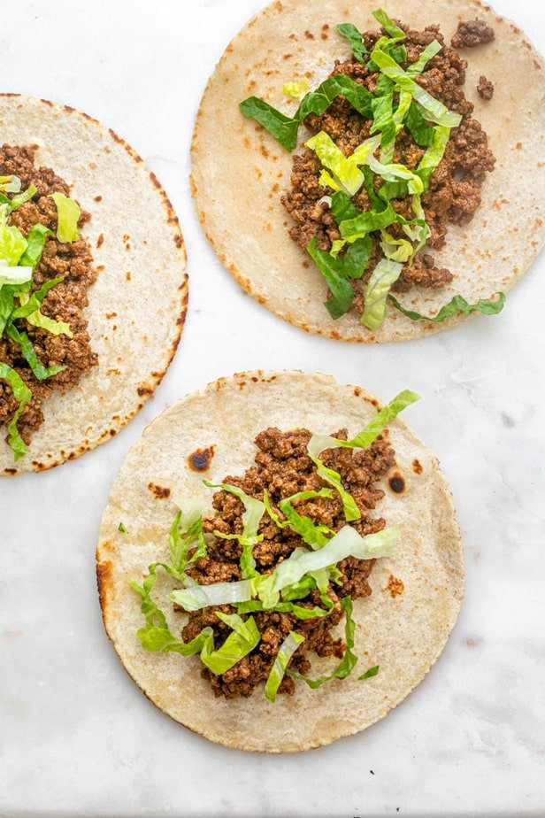 Starting to assemble the tacos with lettuce