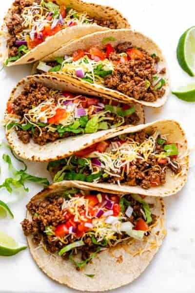 Row of ground beef tacos with colorful toppings, and limes on the side
