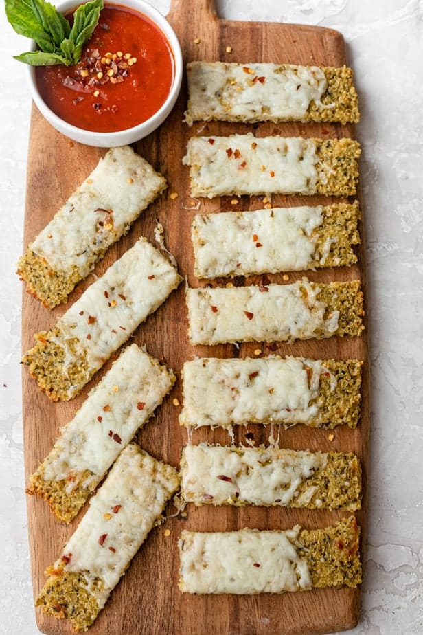 Quinoa Pizza Crust Breadsticks on a cutting board topped with crushed pepper and marinara sauce