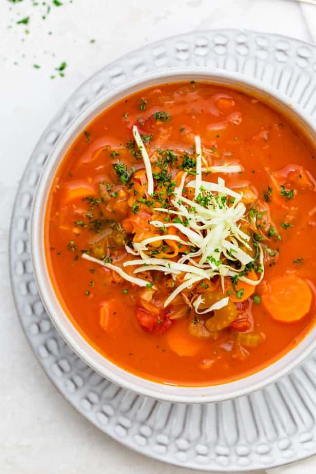 Tomato cabbage soup in a white bowl topped with fresh cabbage