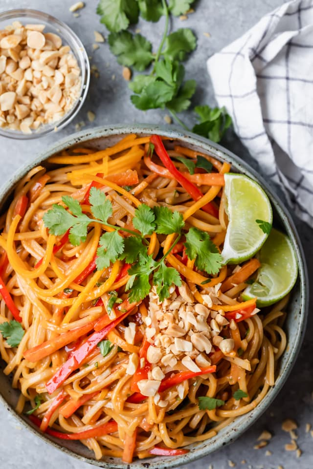 Large bowl of prepared Asian Noodle Salad served with peanuts, cilantro and lime wedges
