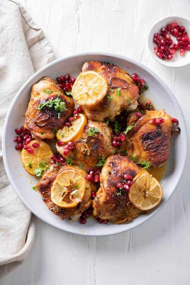 Pomegranate roasted chicken with lemon slices and pomegranate on the side