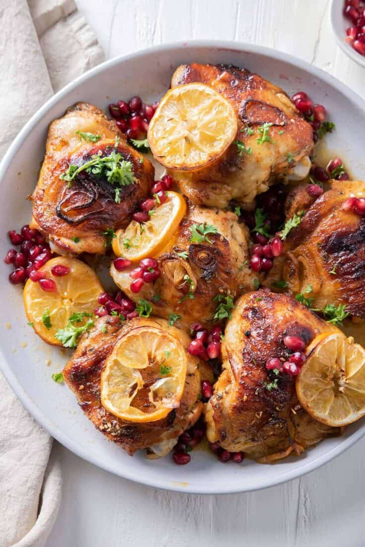 Close up shot of pomegranate roasted chicken thighs topped with lemon slices