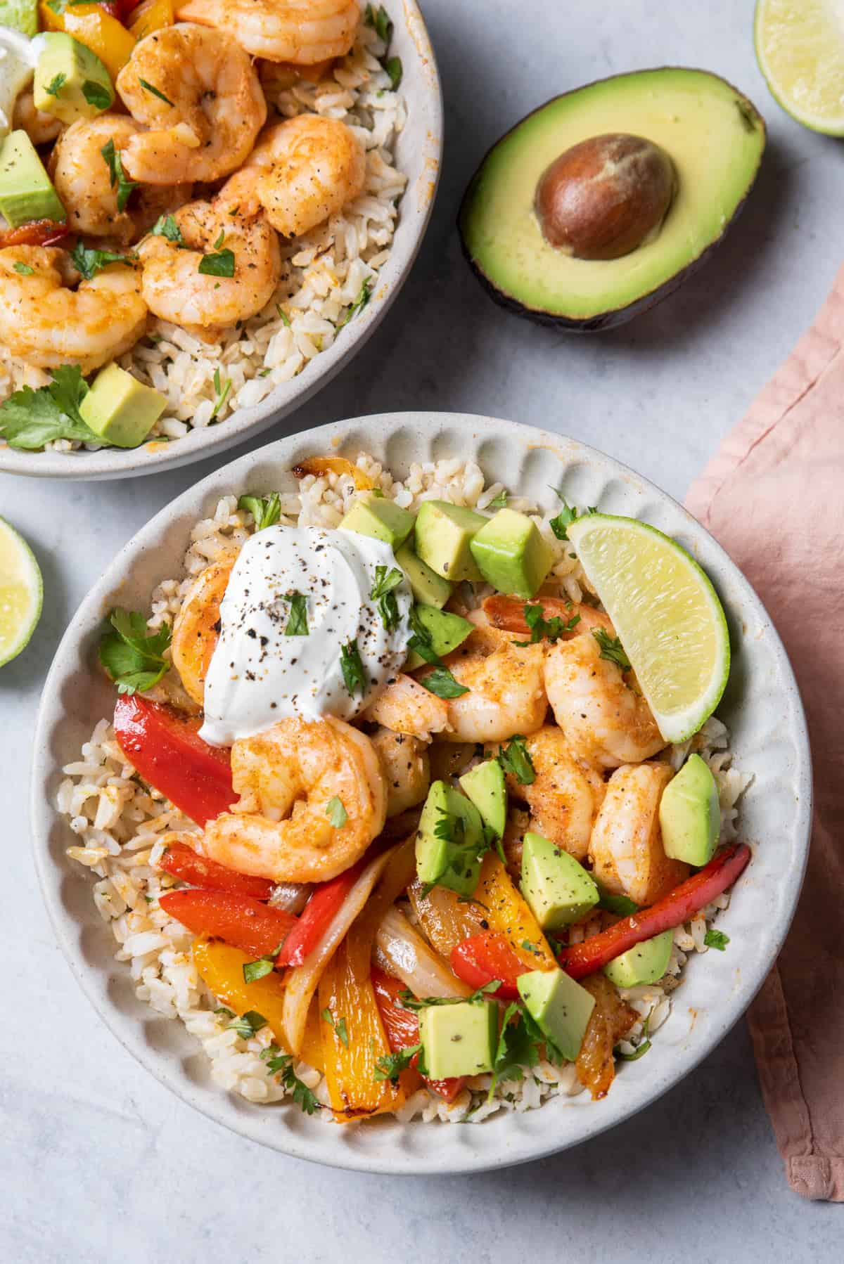 Two bowls of shrimp fajitas served over cilantro lime rice