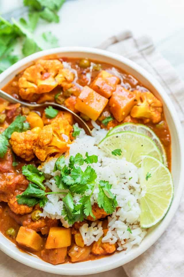 Close up of final cauliflower curry served with rice, cilantro and slices of lime