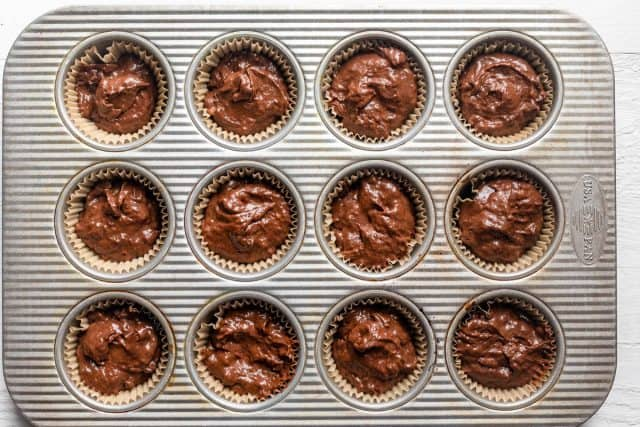 Muffin batter transfered to muffin tin lined with parchment cups