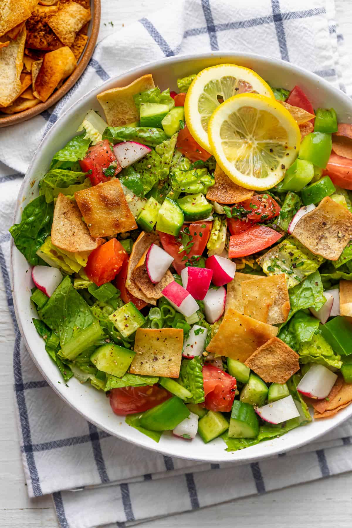Large bowl of Lebanese Fattoush Salad on a marble background. Salad includes lettuce, tomatoes, parsley, cucumbers, green peppers, radishes, green onions and fried pita bread.