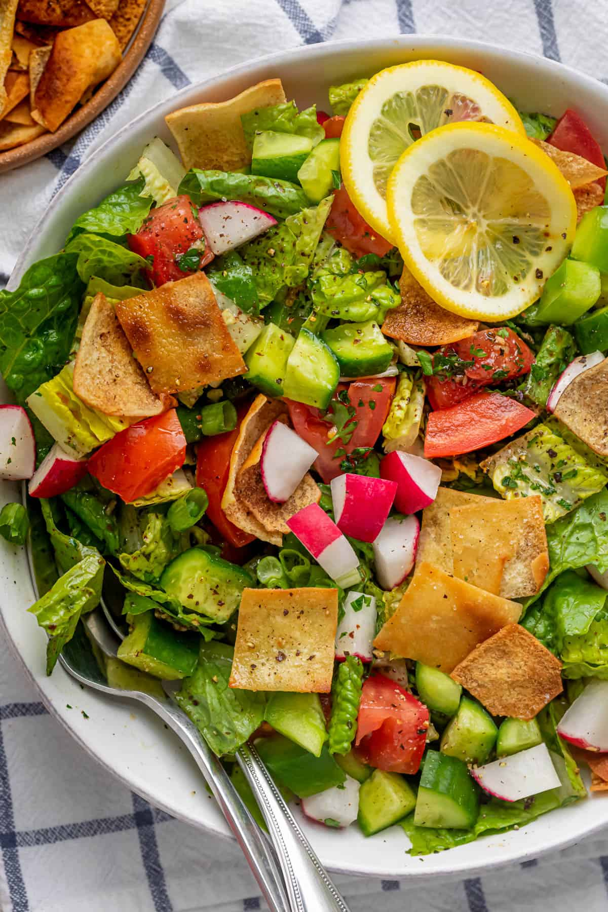 Close up shot of the final fattoush salad with fork and spoon in the bowl for serving