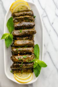 Final stuffed grape leaves lined up on a long plate