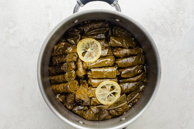 Pot of grape leaves with lemon on top after cooking
