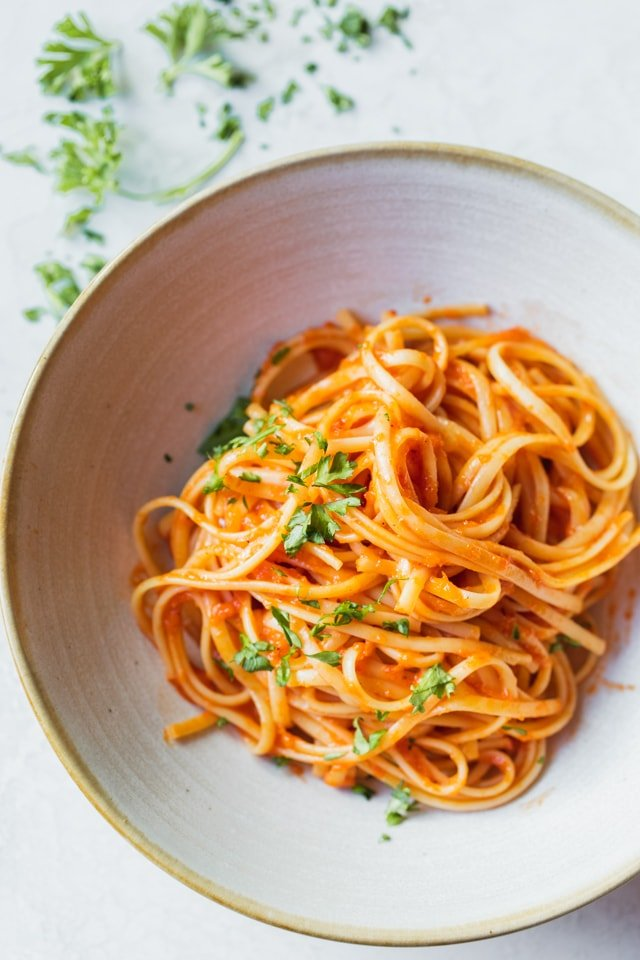 Roasted red pepper pasta served in a large bowl with parsley