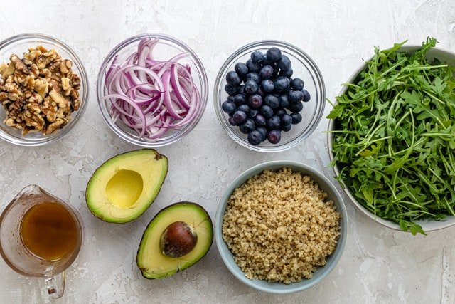 Ingredients to make the recipe: arugula, quinoa, blueberries, onions, walnuts, avocado and dressing