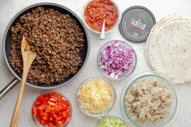 Ingredients for assembly: ground beef, salsa, tomatoes, cheese, onions, cabbage, brown rice and tortillas