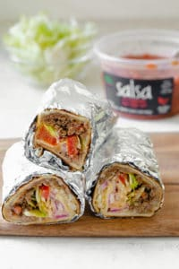 Three burritos stacked on top of each other with salsa in the background