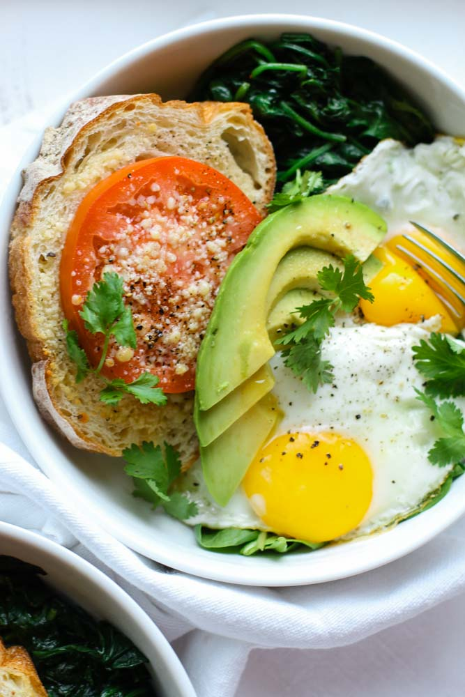 This Blissful Breakfast Bowl is made with sunny side eggs, lemon garlic sauteed spinach, parmesan tomato toast & slices of avocado, drizzled with hot sauce!