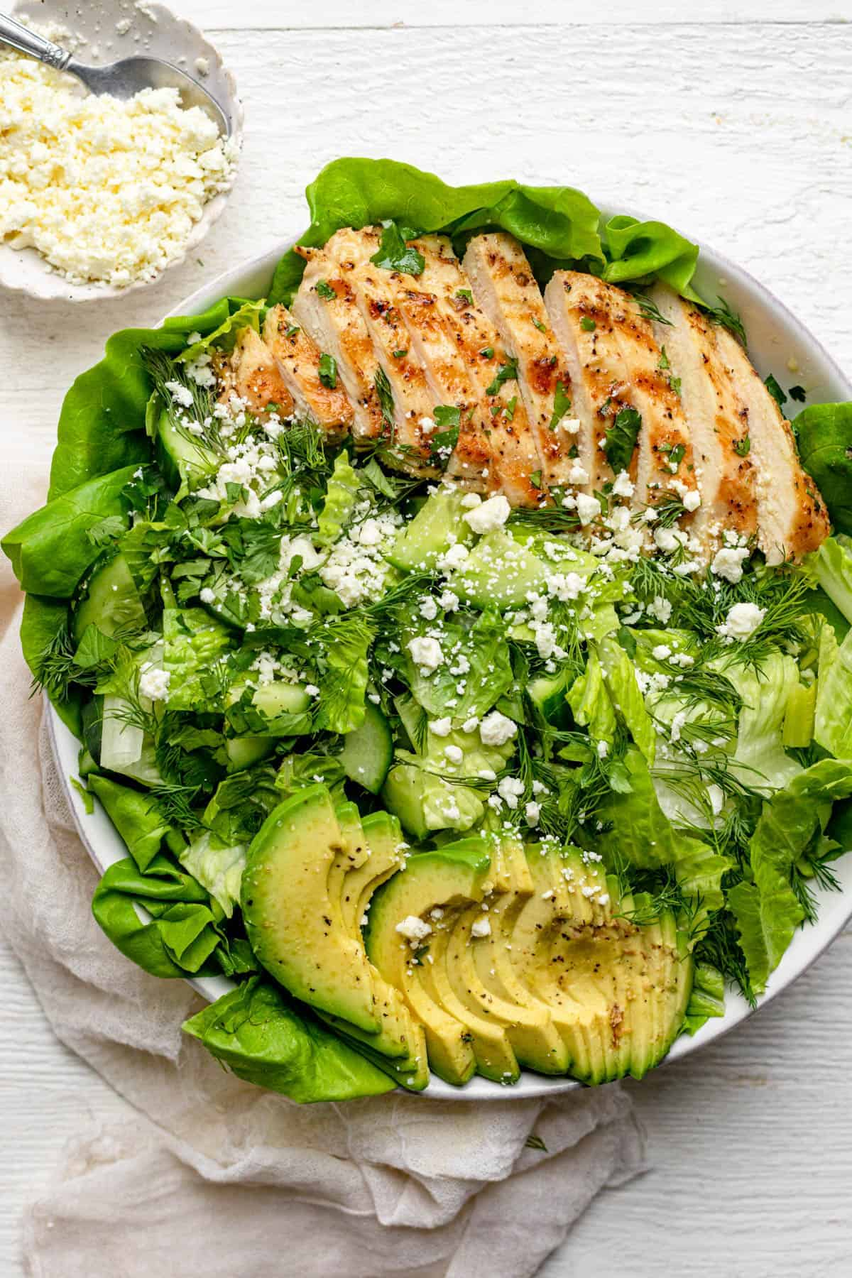 Large bowl of the green goddess salad topped with grilled chicken and avocado