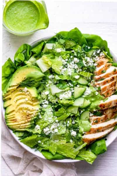 Sliced grilled chicken, sliced avocado, bed of greens in a white bowl plus green cilantro yogurt dressing in a clear jar