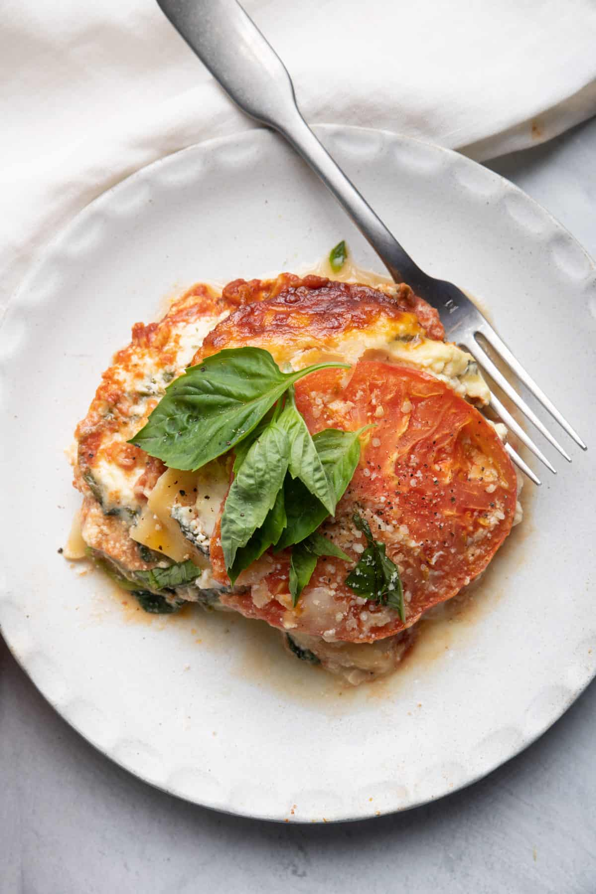 Plate with serving of tomato lasagna topped with basil