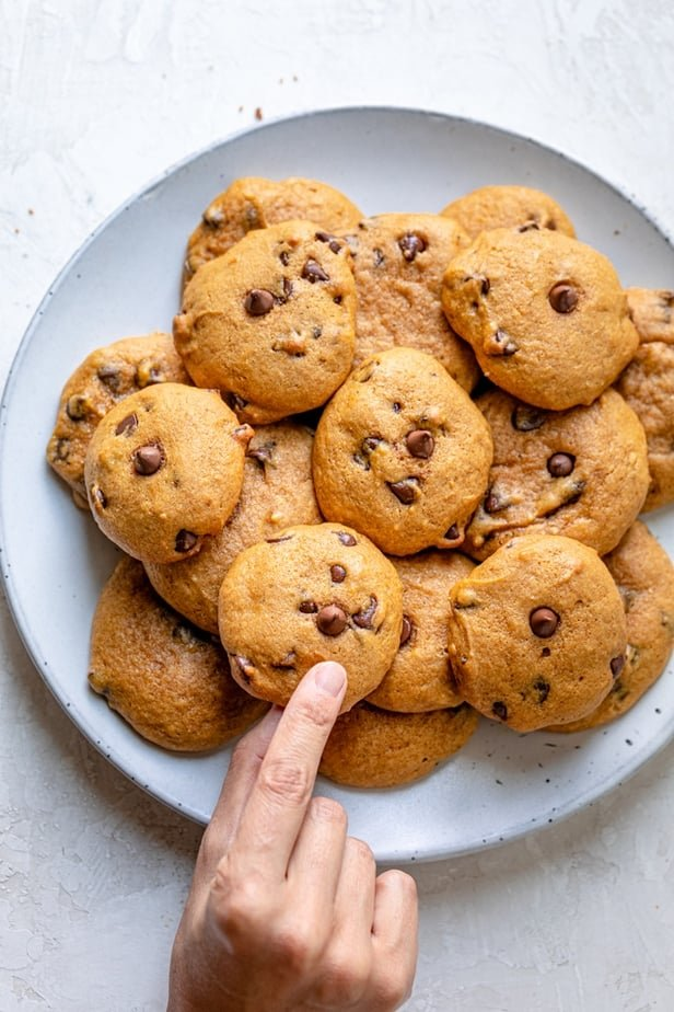Hand grabbing a cookie from a plate full of pumpkin chocolate chips cookies