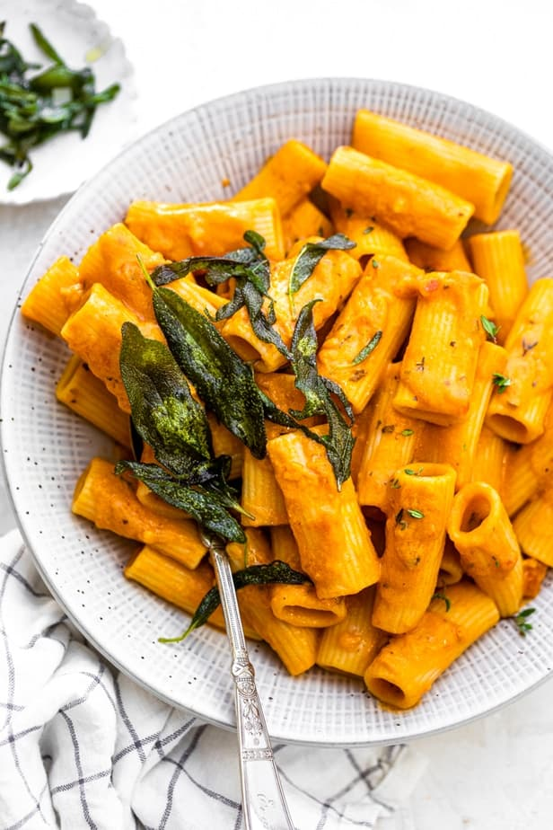 Pumpkin Pasta plated on a gray bowl topped with crispy sage and crushed cashews