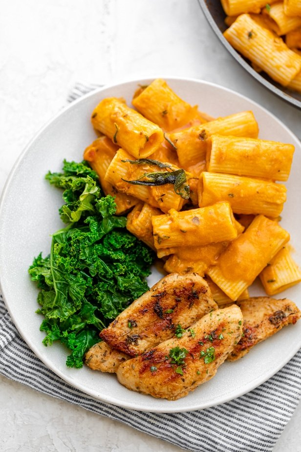 Plate of some of the pumpkin pasta, served with steamed kale and grilled chicken