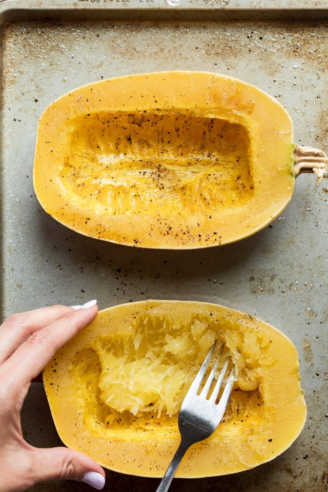 Two spaghetti squash halves face up on a baking sheet. Fork teasing one of them to pull apart the strands