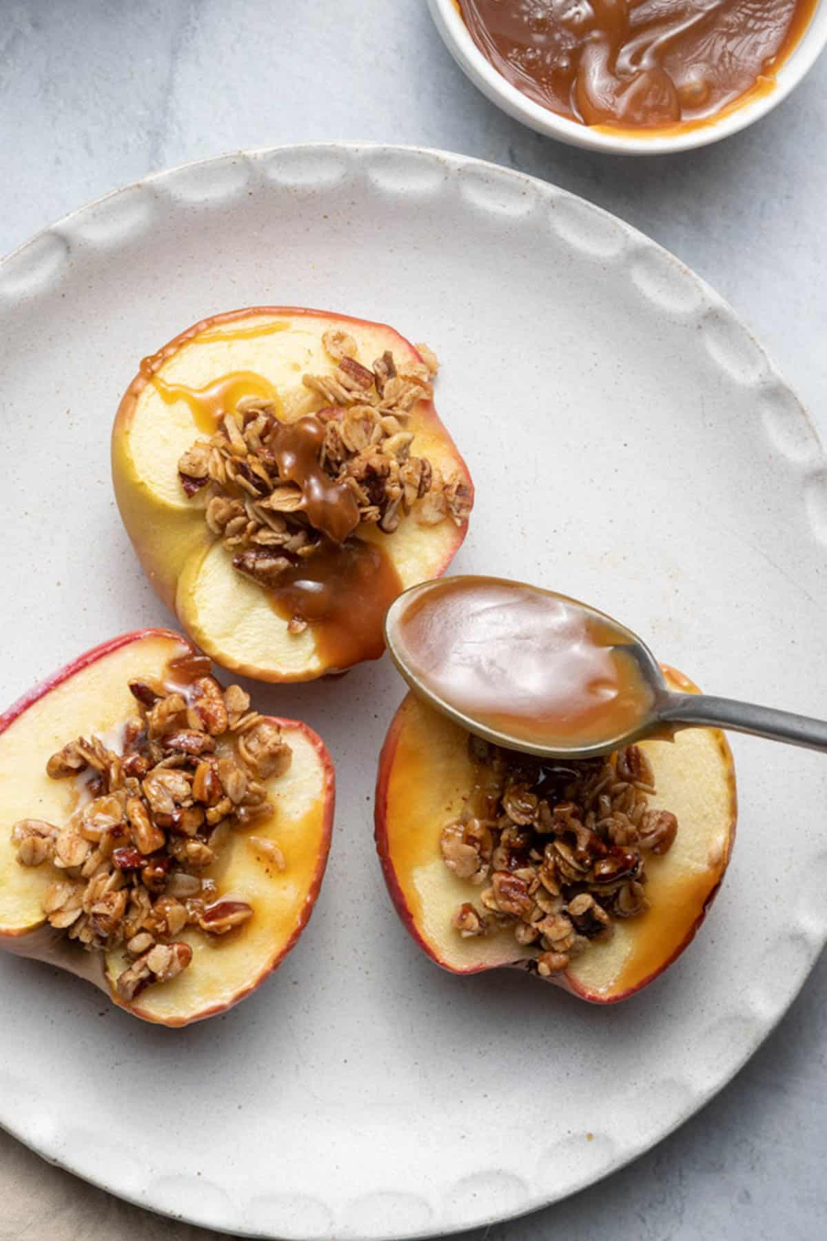 Spoon with caramel sauce going over the cinnamon bakedapples