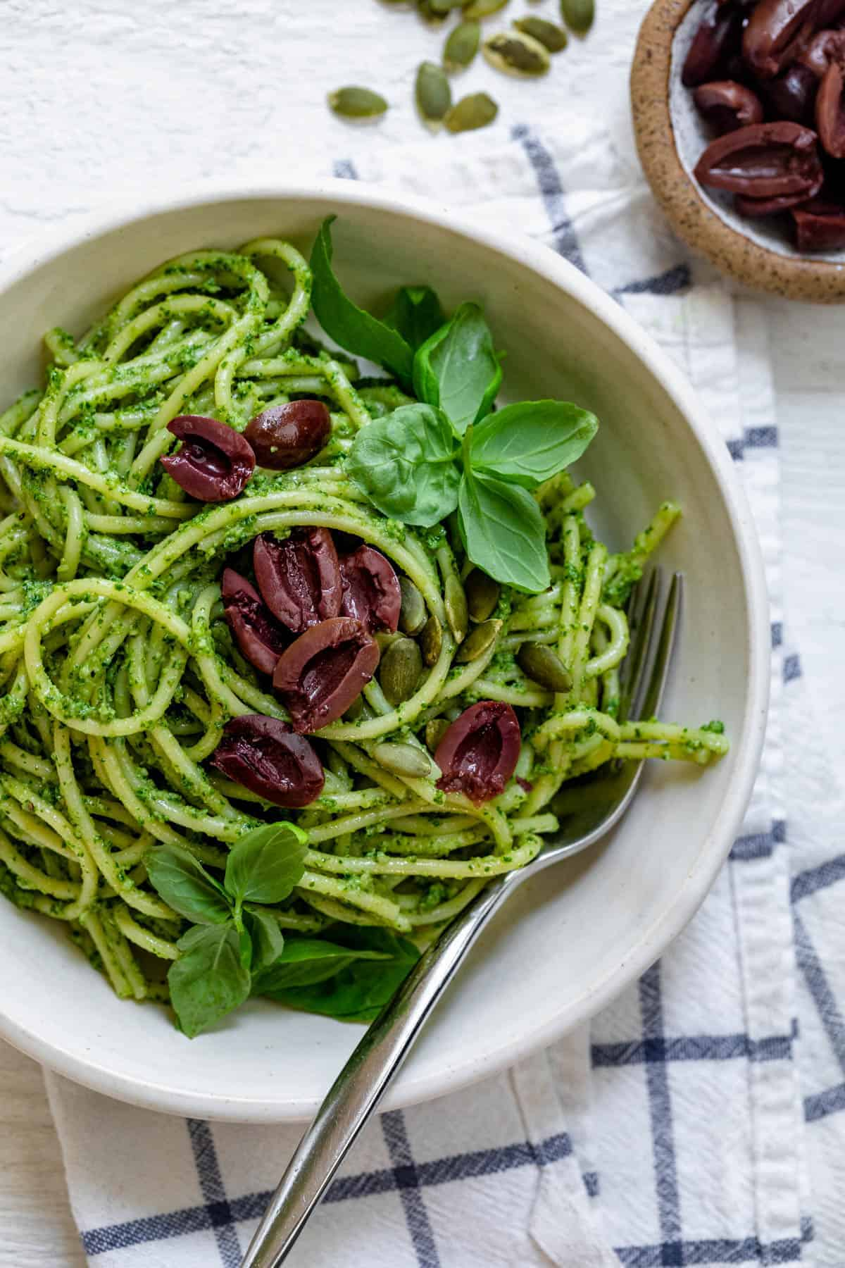 Pumpkin seed pesto pasta topped with kalamata olives
