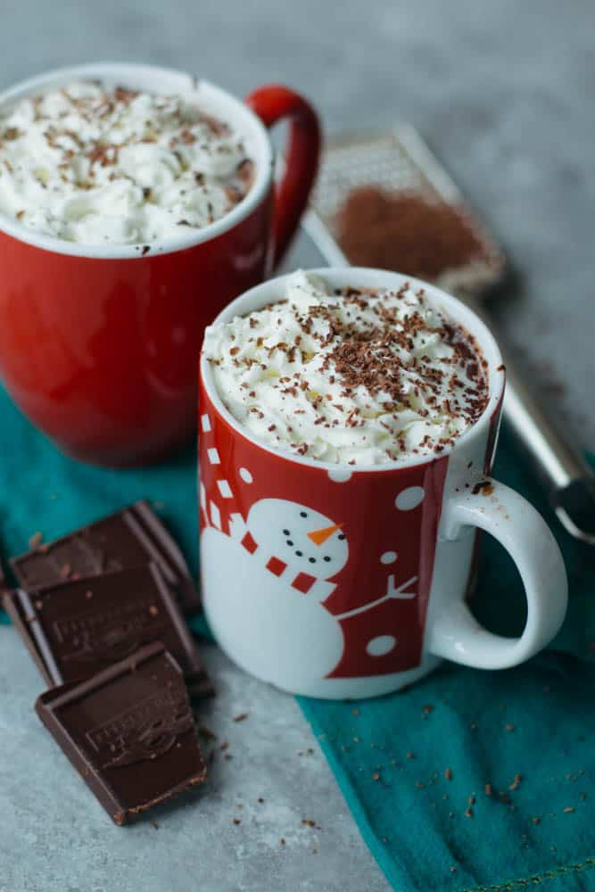 Vegan hot chocolate in two red mugs topped with whipped cream and shaved chocolate