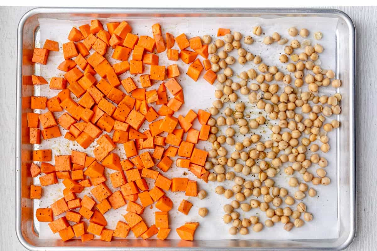 Cubed sweet potatoes and dried chickpeas on a baking dish lined with parchment paper