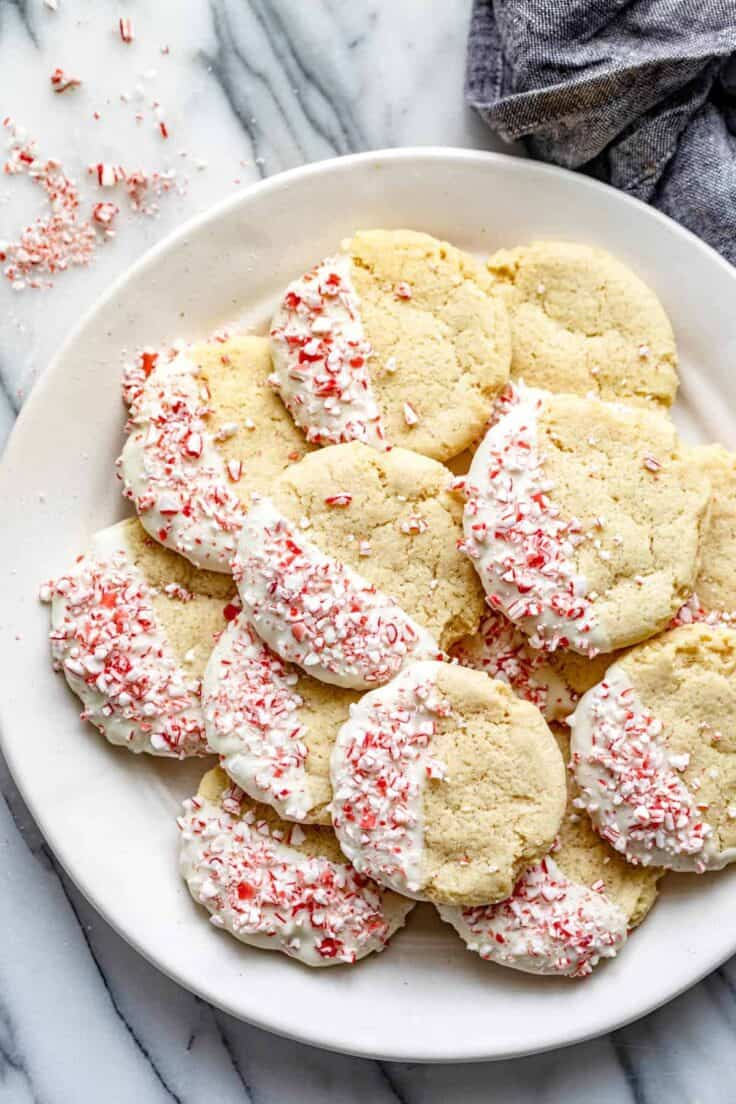 White plate on marble background of sugar cookies dipped in white chocolate