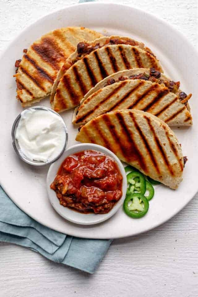 4 small bean and cheese quesadillas on a plate served with sour cream and salsa