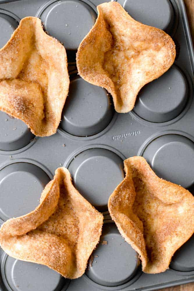 This homemade Cinnamon Sugar Tortilla Bowls uses the underside of a muffin tin as a mold to bake and create the cutest bowls. They are made by sprinkling cinnamon & sugar on tortillas and baking them in the oven until golden and crisp. You can use them as ice cream serving bowls and add the toppings of your choice!