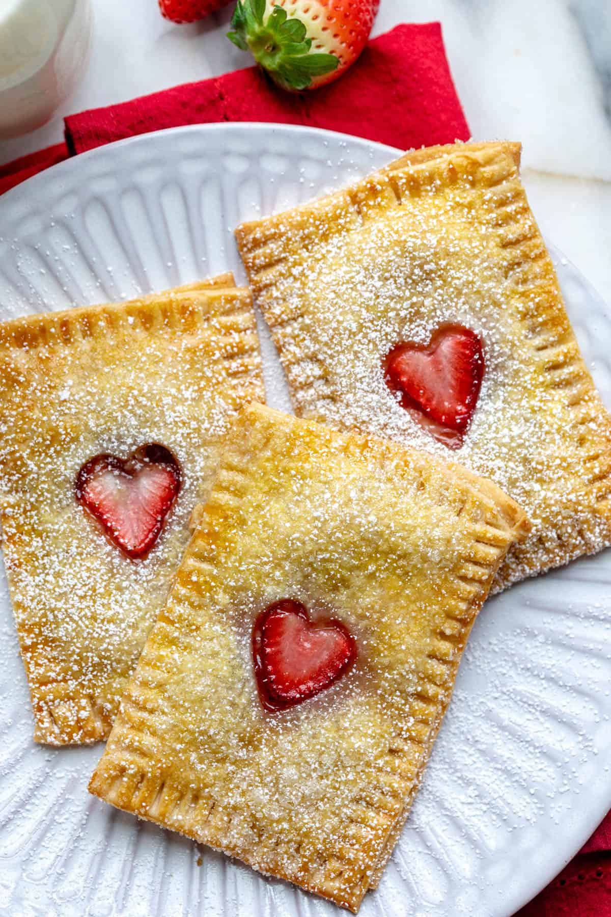 Close up of 3 homemade pop tarts with hearts cut out sprinkled with powdered sugar