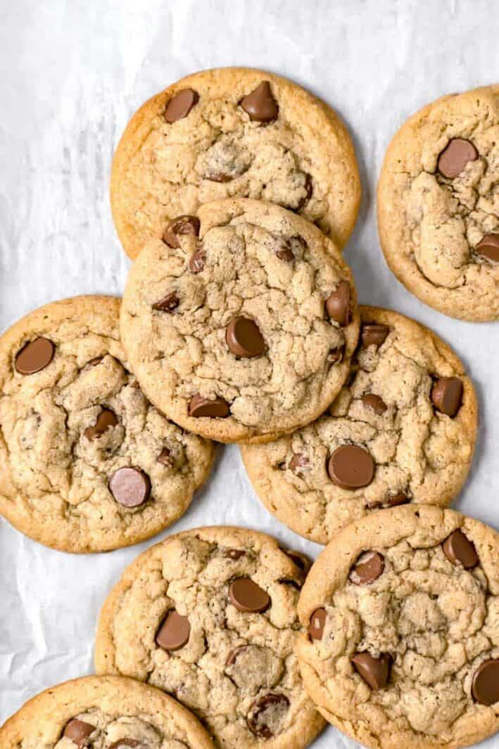 Close up shot of many tahini chocolate chip cookies on a parchment paper background