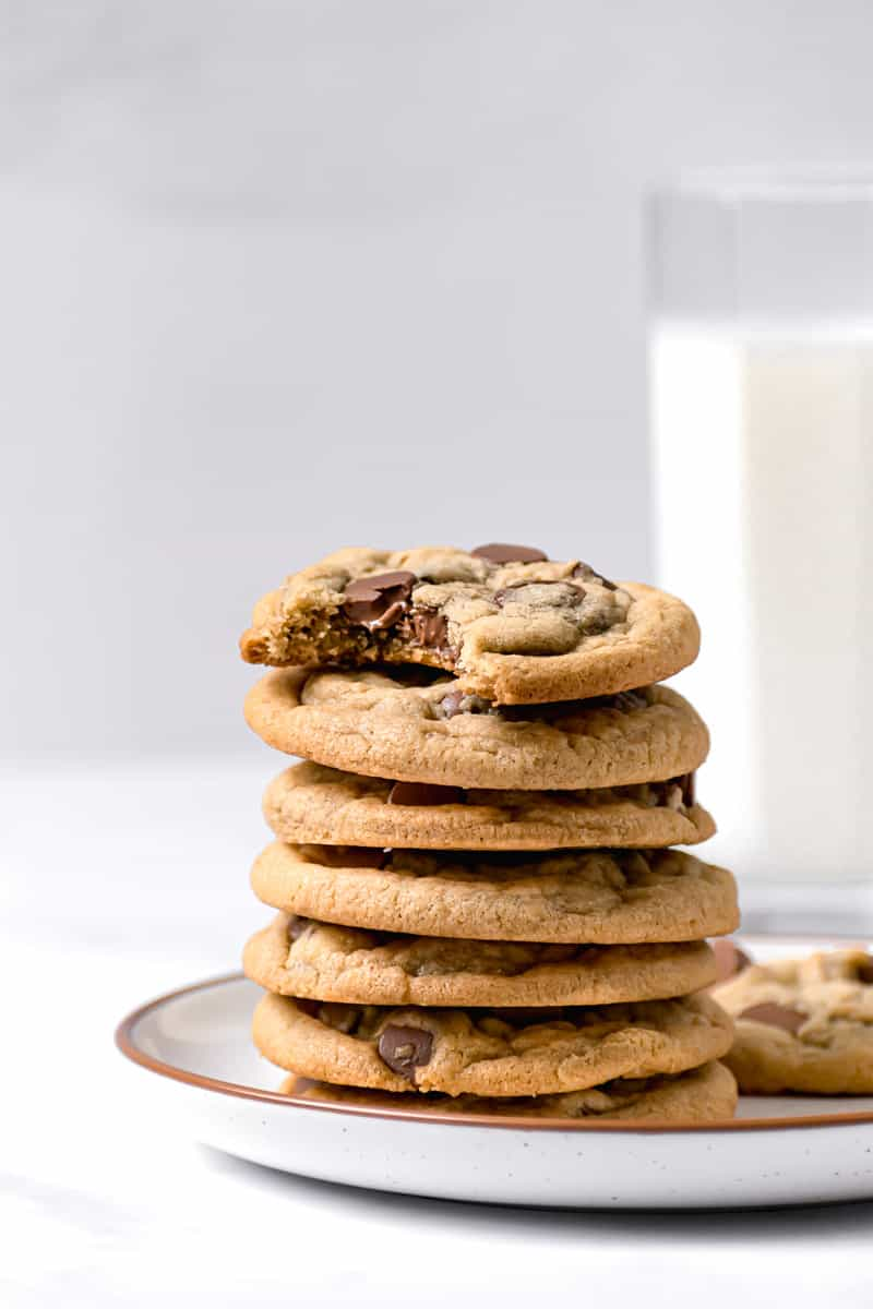 Stack of chocolate chip cookies on a plate with glass of milk in the background