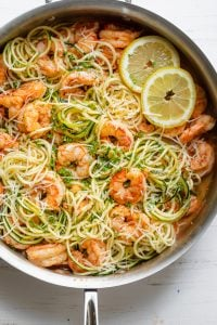 Healthy shrimp scampi made with half pasta and half zucchini topped with lemon slices