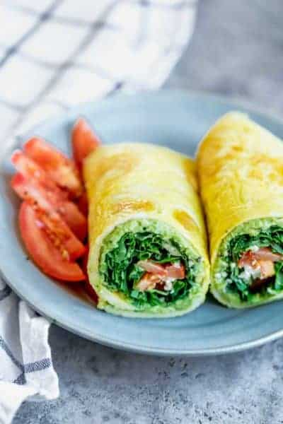 This low carb egg wrap is a power house breakfast option when you're trying to limit eating bread, but want to feel full and satisfied. I make the egg wrap by whisking eggs with flour and water, frying it on a pan and stuffing it with veggies, herbs and cheese. It's totally customizable to your taste and diet goals!