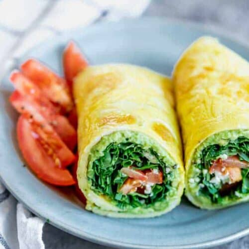 A couple of low carb egg wraps on a blue plate with sliced tomatoes
