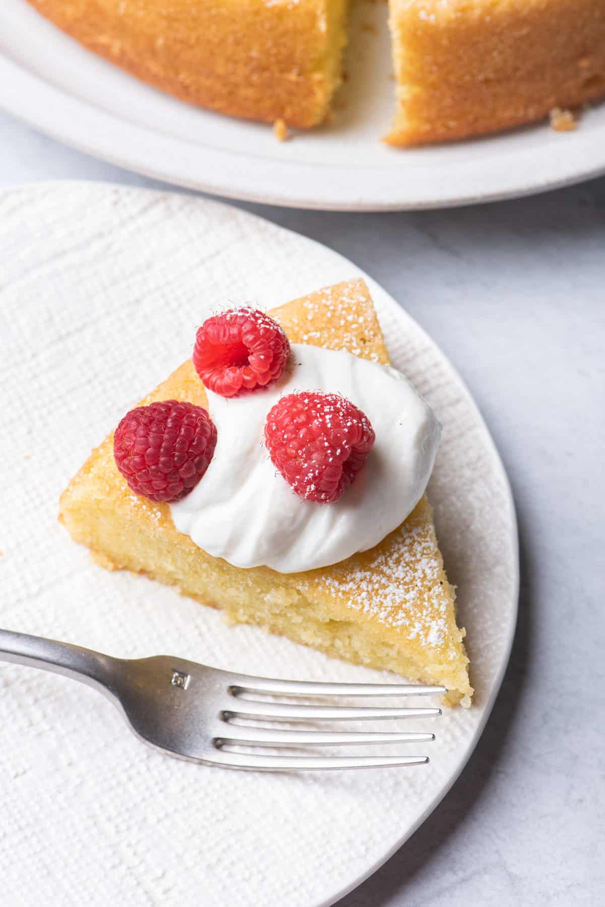 Slice of olive oil cake on a small plate topped with whipped cream and raspberries